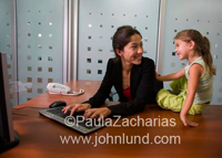 Hispanic office worker woman with her young daughter with her in the office. Happy and fun.
